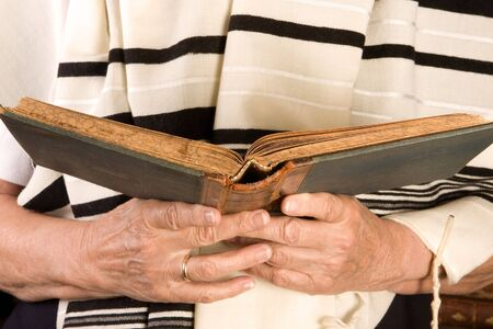 jewish prayer: Hands holding a jewish prayer book wearing a prayer shawl