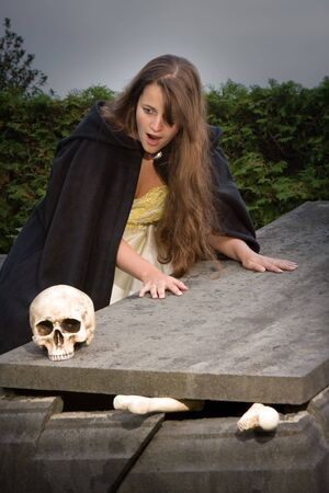 Young woman finding a skull on a broken tombstone in a cemetery Stock Photo - 5495810