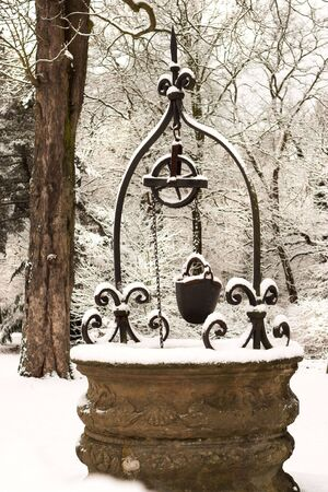 water well: Beautiful old water well in a park, on a snowy winter day Stock Photo