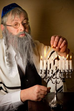 Old jewish man lighting candles of a hannukah menorah photo
