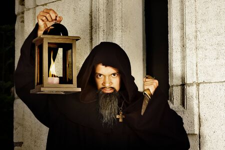 cloak and dagger: Halloween scene of an evil monk with dagger and lantern