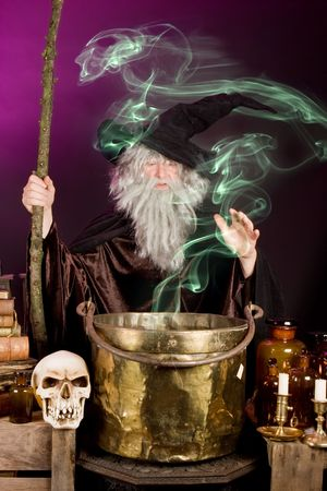 Green ghost leaving the cooking pot of a halloween sorcerer photo