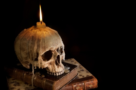 terror: Halloween image with a burning candle on an ancient skull