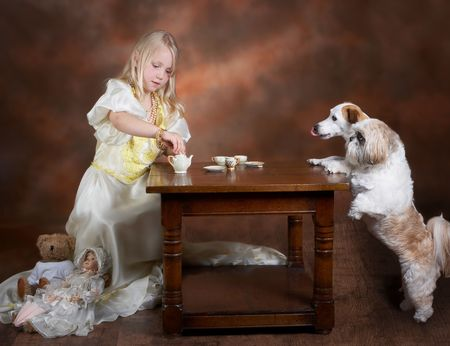 Little blond girl having tea with two dog, dressed in a vintage ball-gown Standard-Bild