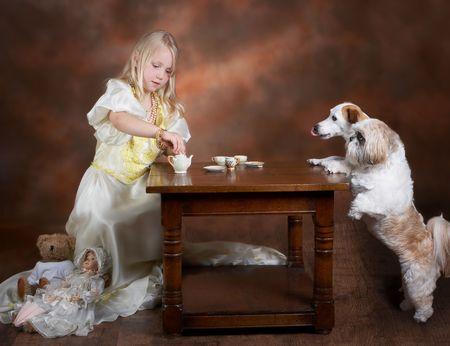 niños vistiendose: Niña rubia con té con dos perros, vestido con una bata de bola vintage