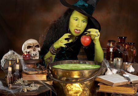 bruja: Bruja verde Halloween poner una manzana roja en un caldero con sopa de t�xicos Foto de archivo