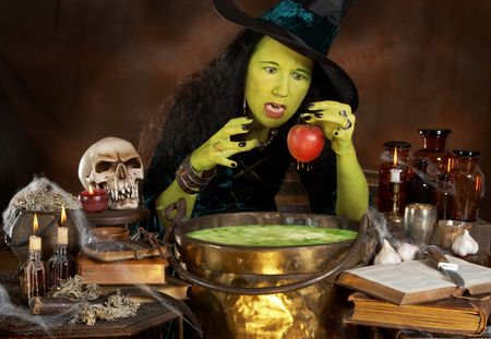 spells: Green halloween witch putting a red apple in a cauldron with poisonous soup Stock Photo