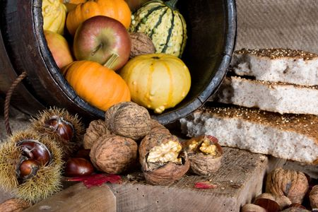 Wooden bucket filled with autumn products, and traditional bread photo