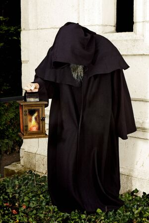 robe: Halloween scene of a hooded monk holding a lantern