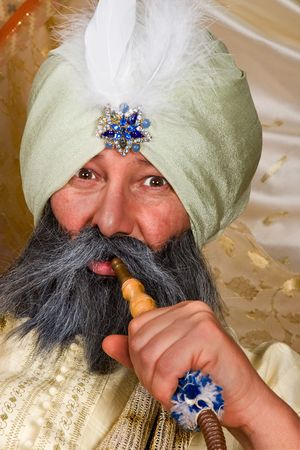 pipe smoking: Arabian turban sultan with a water pipe