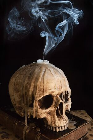 Halloween image with a smoking candle on an ancient skull photo