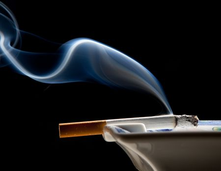 Cigarette on ashtray with a beautiful wisp of smoke photo