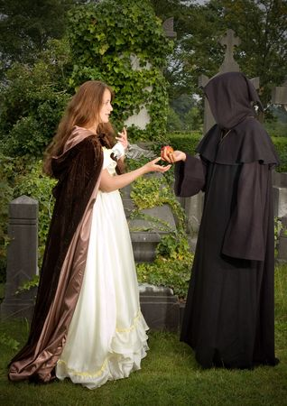 cloak: Halloween scene of an evil monk offering an apple to a victorian woman Stock Photo
