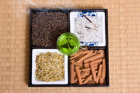 Various herbs, incense and green tea on a traditional japanese tatami mat photo