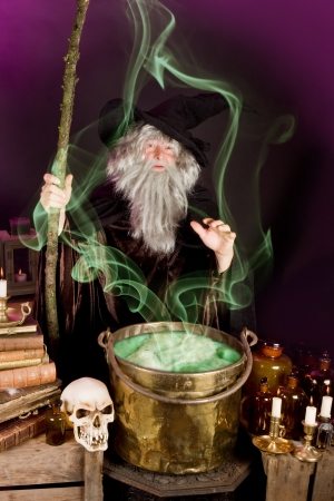 Evil sorcerer casting a spell on green poison soup photo