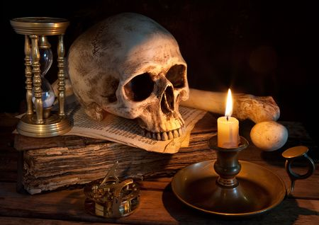 Vintage skull on antique book with candle and hourglass photo