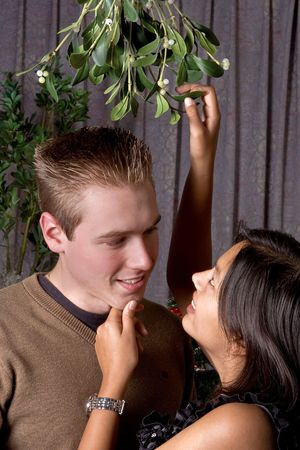 Attractive brunette asking for a kiss under the christmas mistletoe photo