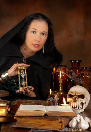 wicca: Halloween sorceress showing a hourglass and witchcraft books Stock Photo
