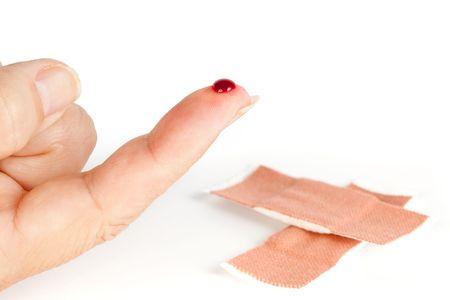 herida: Closup de un dedo de sangrado herido y una fuera de foco baind-ayuda  Foto de archivo