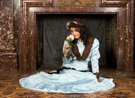victorian fireplace: Portrait of a beautiful young victorian lady in front of a castle fireplace. Shot in the antique castle Den Brandt in Antwerp, Belgium (with signed property release for the Castle interiors). Stock Photo