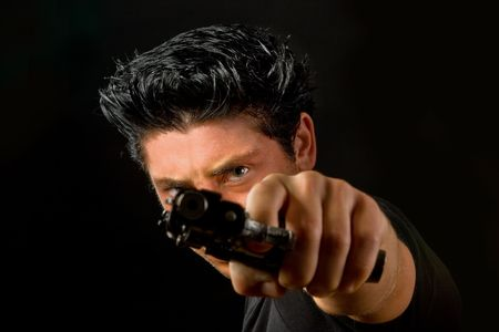 Portrait of a young man pointing a weapon at the camera Stock Photo - 5674507