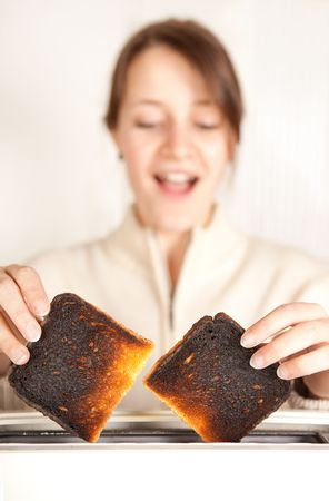 burnt toast: Surprised woman taking burnt toast out of a toaster Stock Photo