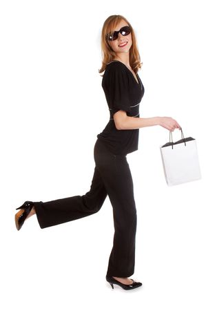 chanel: Smiling young woman walking in a black outfit, with a little shopping bag Stock Photo
