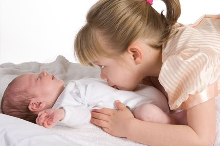 big and small: Little sister caressing her 15 days old brother Stock Photo