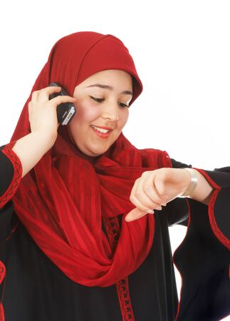 purdah: Young veiled woman looking at her watch while making a phone call