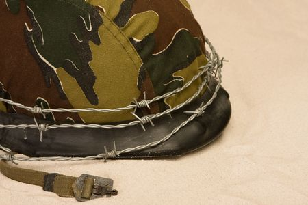Helmet with barbed wire lying in the sand photo