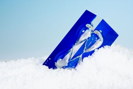 expiring: Modern blue sand timer lying in the snow