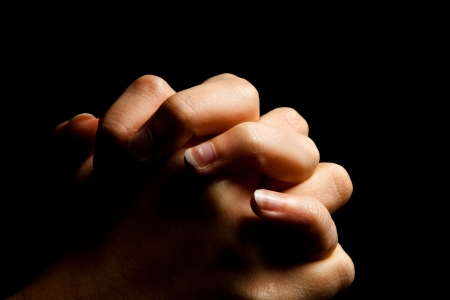 prayer: Female hands folded in prayer in darkness