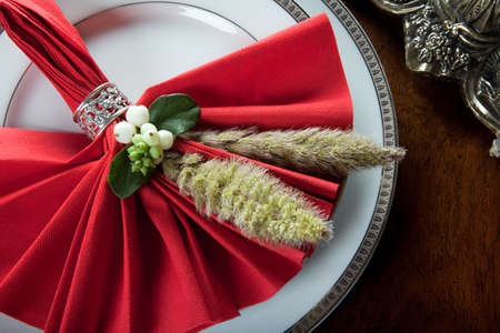 Festive red decorated napkin with ornate sterling silver napkin ring photo
