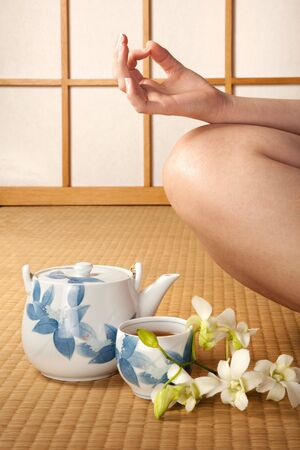 Meditating woman on japanese tatami mat with orchids and green tea