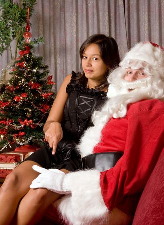 provocative couple: Naughty santa claus with his hand on the thigh of an attractive brunette