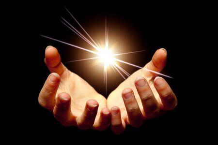 manos abiertas: Manos de mujeres sosteniendo una estrella brillante en la oscuridad