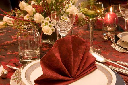 cena navide�a: Tabla de cena de Navidad con velas, flores y servilletas rojos  Foto de archivo