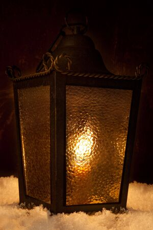 Lantern on snow with burning candles inside photo