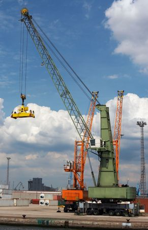 docker: Container crane going down to grab one more container and carry it into a ship (all brand names and logos have been carefully removed)