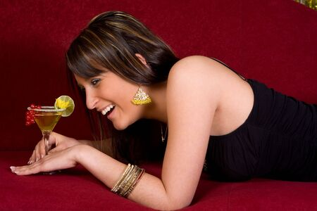 Young woman smiling on a couch holding a fruit cocktail Stock Photo - 6034021