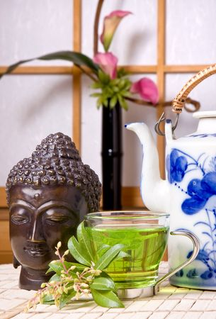 ikebana: Buddha, green tea and ikebana flowers against a japanese traditional shoji window