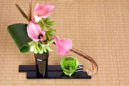 ikebana: Ikebana Japanese flower arrangement and green oriental tea Stock Photo
