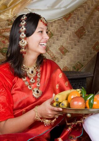 Young Indian beauty in saree offering fruit photo