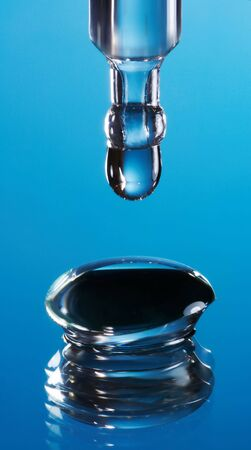 Extreme macro of an eye dropper dropping cleansing fluid into a contact lens photo