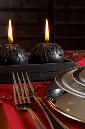 Detail of a christmas dinner table with red napkins and black candles photo