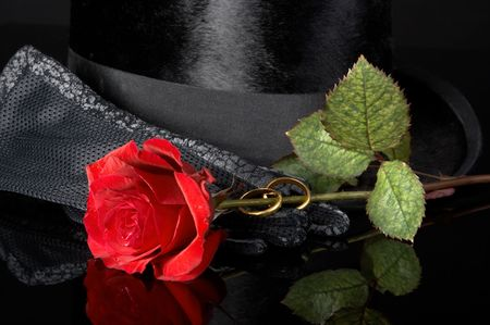 Black top hat, fancy gloves, a red rose and wedding rings photo