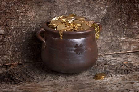 bucket of money: Pot of gold against a tree bark background Stock Photo