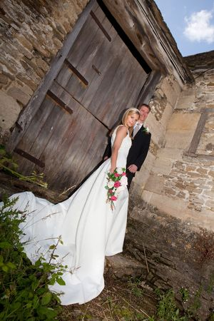 Young wedding couple against a grunge medieval wall Stock Photo - 6166256