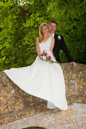 Loving newly wed couple posing on a medieval grunge packhorse bridge photo