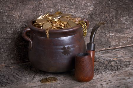 Old wooden pipe and antique ceramic pot filled with gold photo